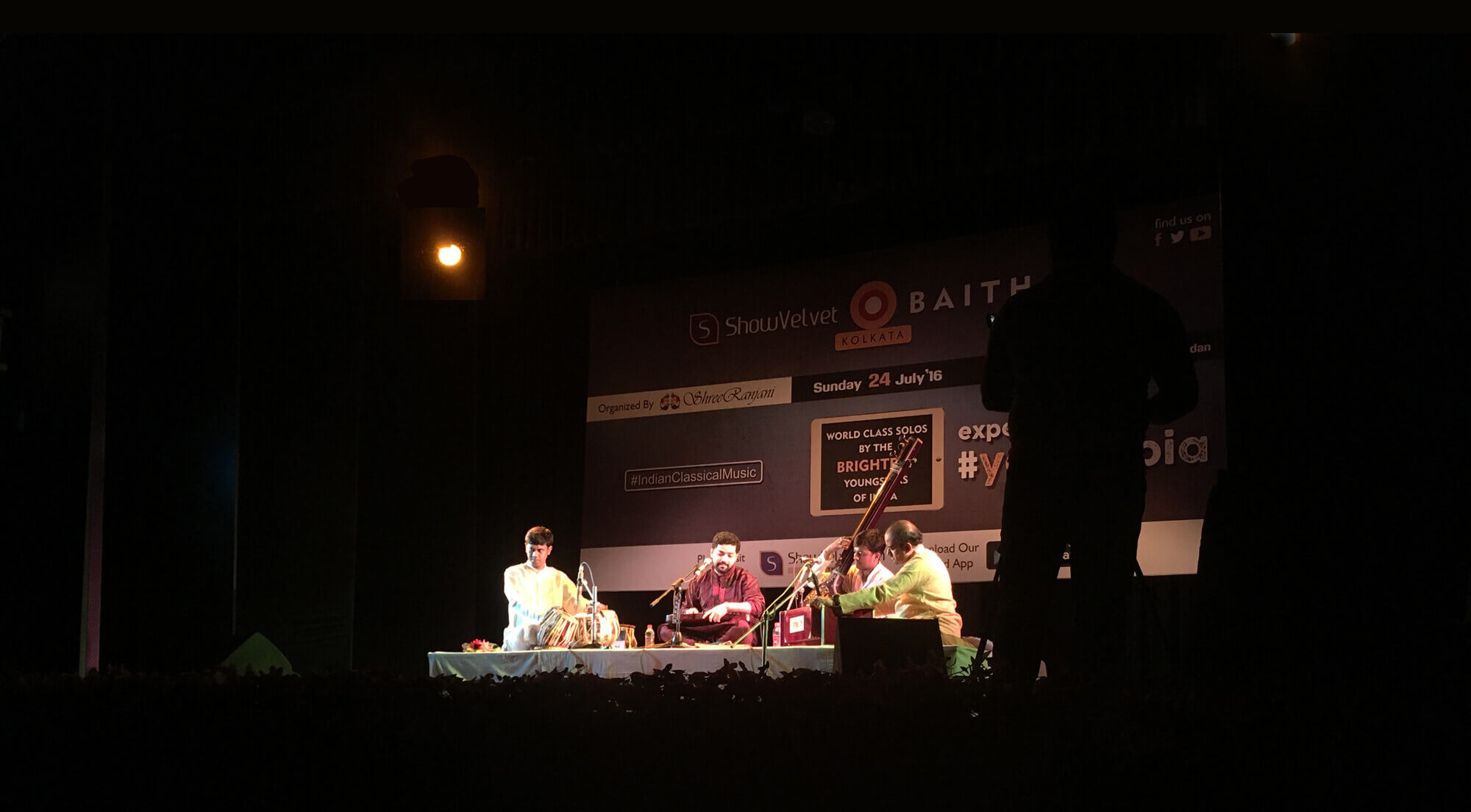 Photo of the stage Samrat Pandit performing with tabla, harmonium and tanpura