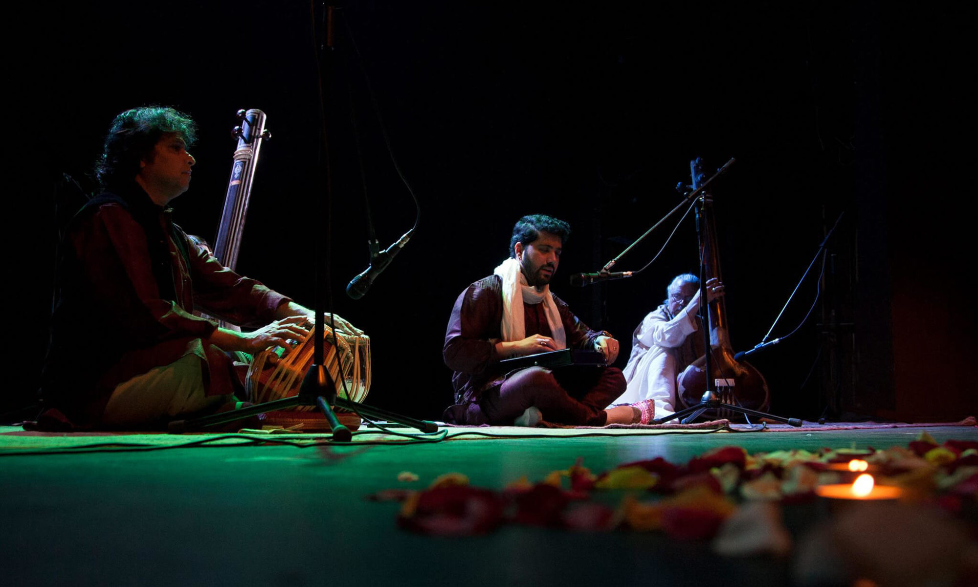 Samrat Pandit Promo Shot on stage with tabla and tanpura players in the shade with candles